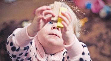 Young girl holding jenga blocks