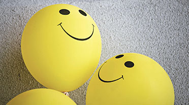 3 yellow balloons with smiley faces