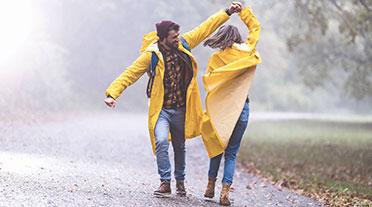 Couple dancing in the rain wearing yellow rain coats