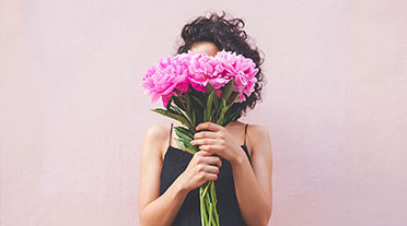 Young woman holding pink flowers