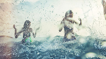 Two women in the sea with water splashing