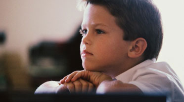 Young Boy with ADHD Resting Chin on Hands