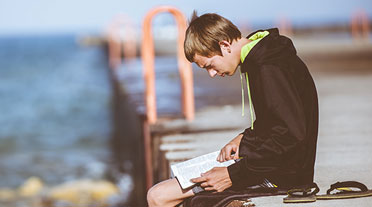 Boy Sat on Dock Reading ADHD Book