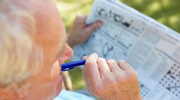 Gentleman with Dementia Doing Newspaper Crossword